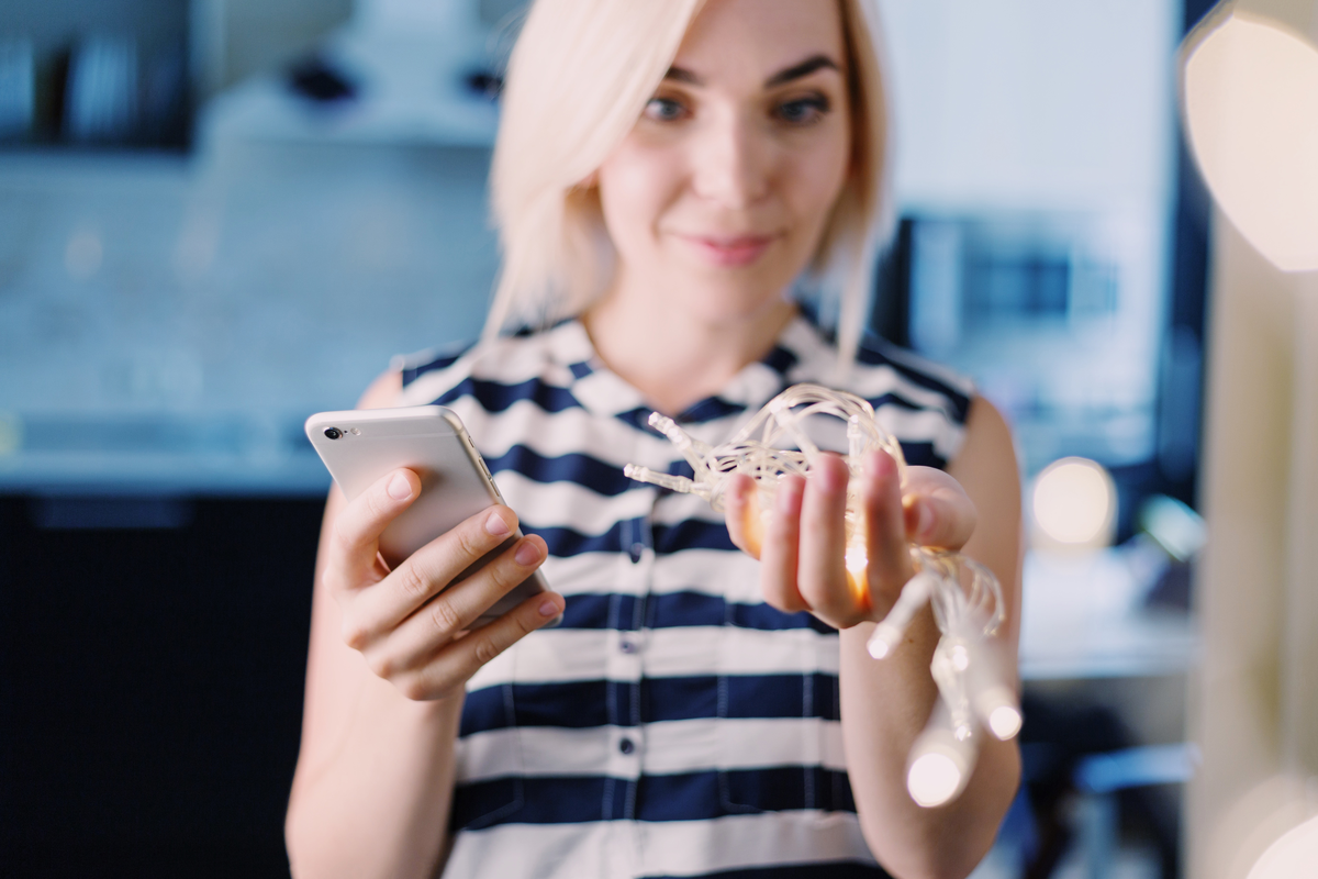 Woman holding phone and earbuds