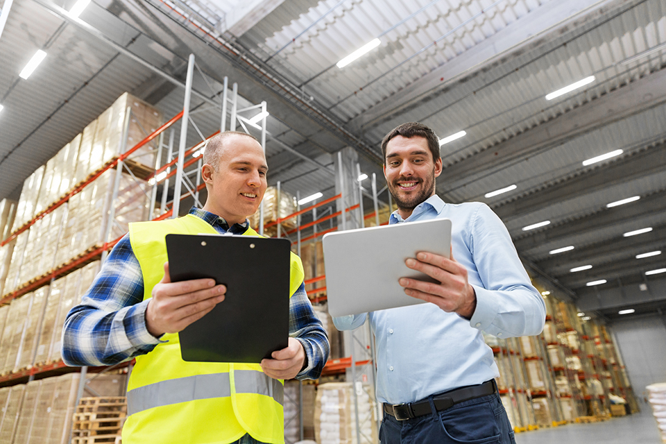 warehouse worker with clipboard talking to businessman with tablet