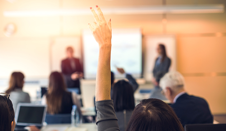 woman raises hand in training course