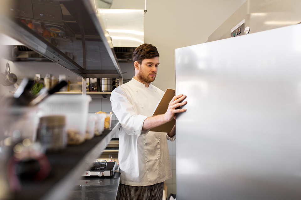 chef opening fridge in commercial kitchen