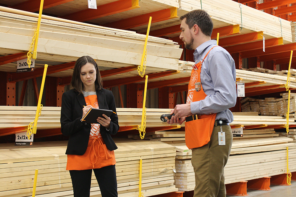 Employees assessing energy use in the lumber aisle of the Home Depot