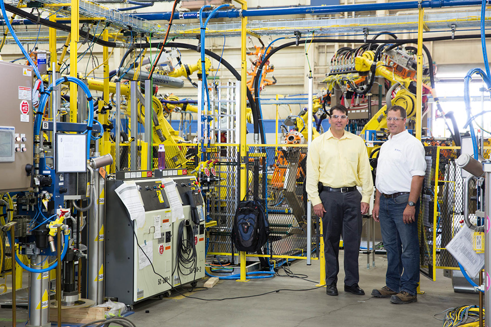 two men standing near energy-efficient technology at the Valiant TMS facility