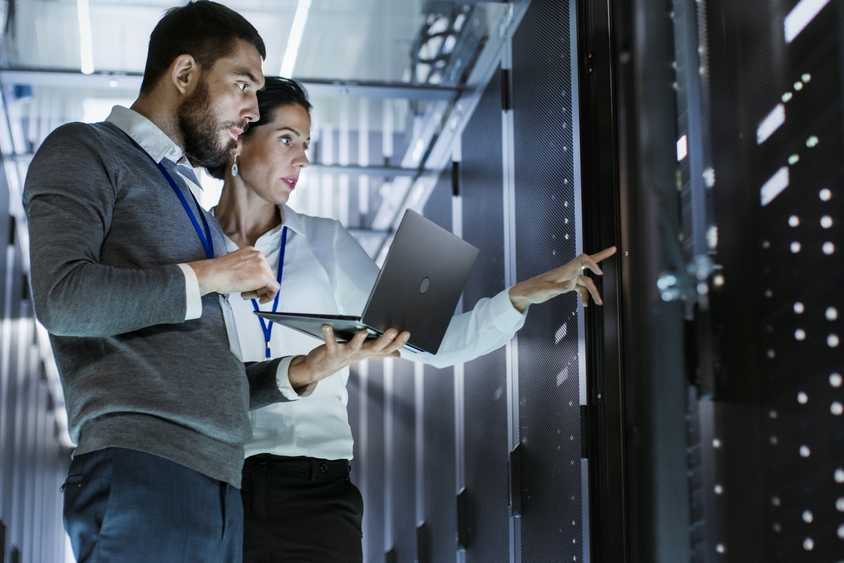 two employees inspecting IT systems at a data center