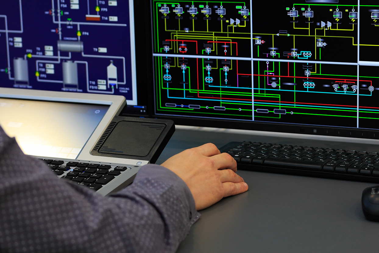 A hand working with a computer that is displaying energy data