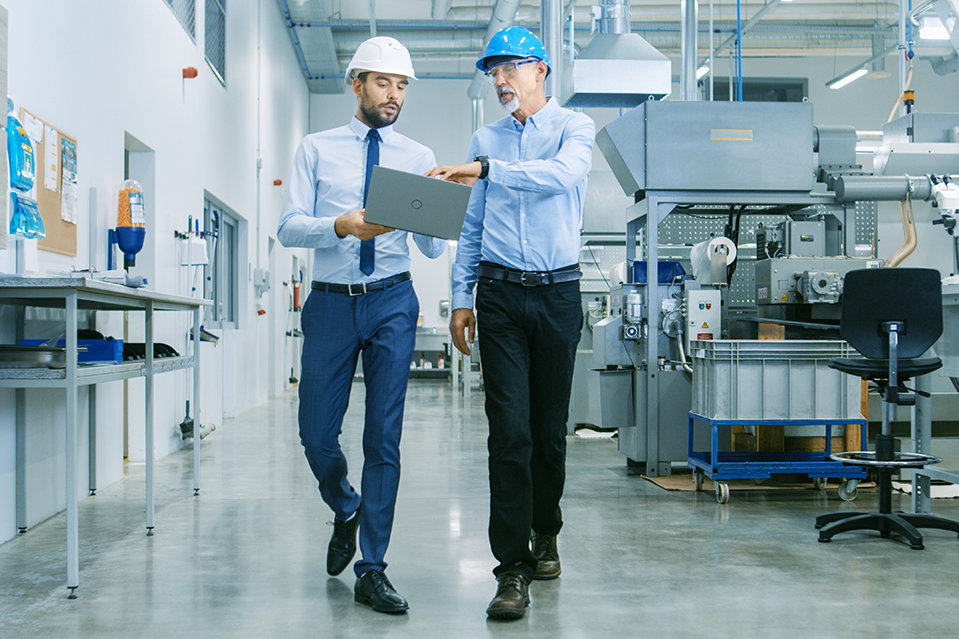 Two men in suits and hard hats walking through their workplace, discussing how to optimize systems.