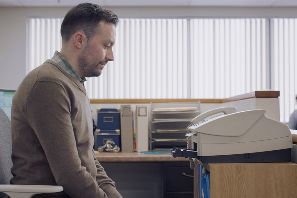 man waiting for an inefficient office fax machine to send a fax
