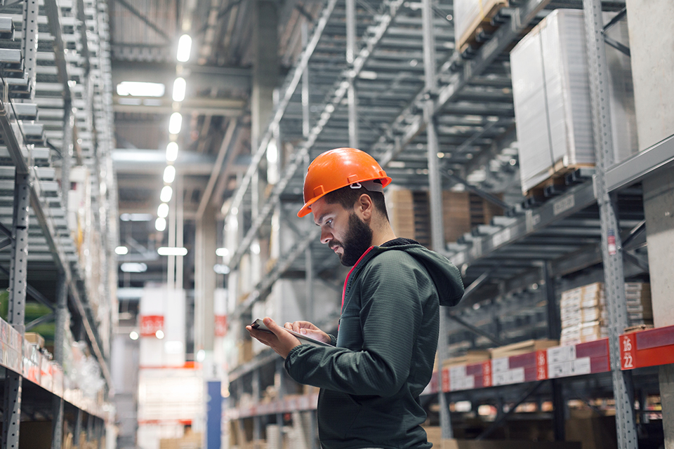 warehouse worker wearing hard hat while using an electronic tablet