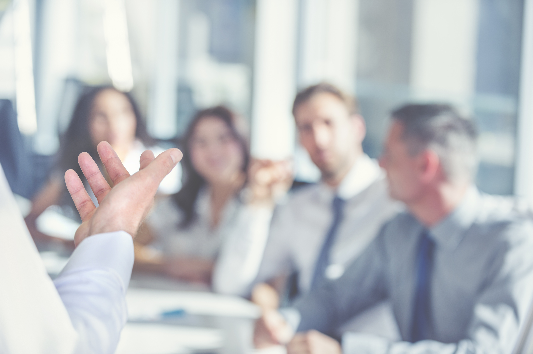 man presenting to colleagues in meeting room