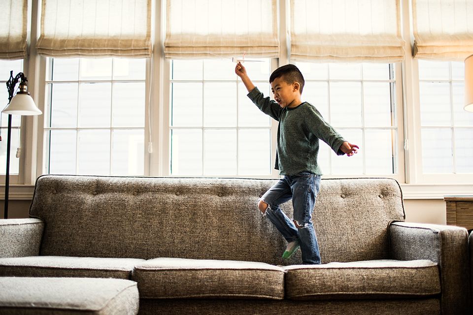 Boy jumping on sofa in front of living room windows