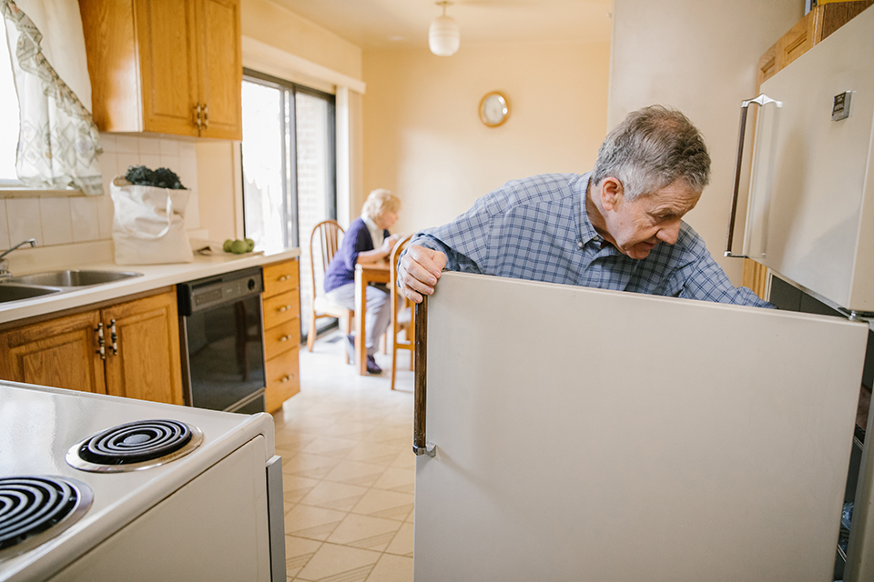Elderly man opening fridge