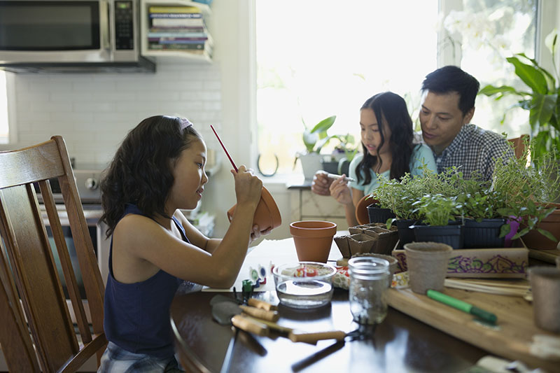 family painting clay garden pots together