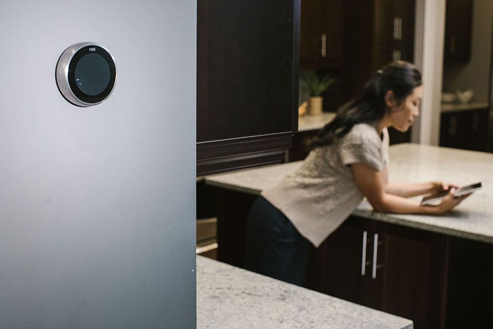 woman controlling her smart thermostat from her smart phone at home