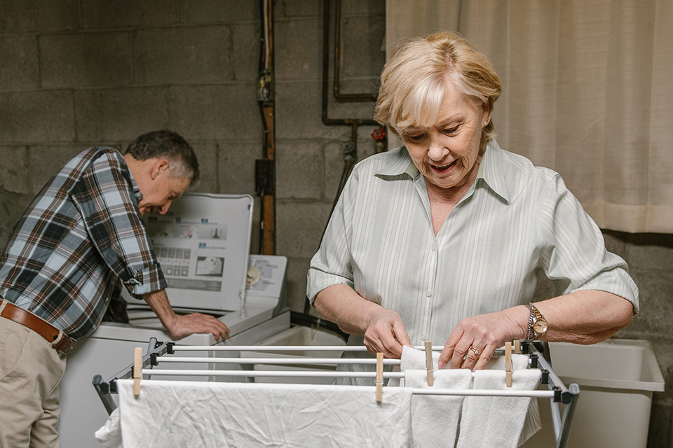Retired couple doing laundry by hanging washed load onto a drying rack