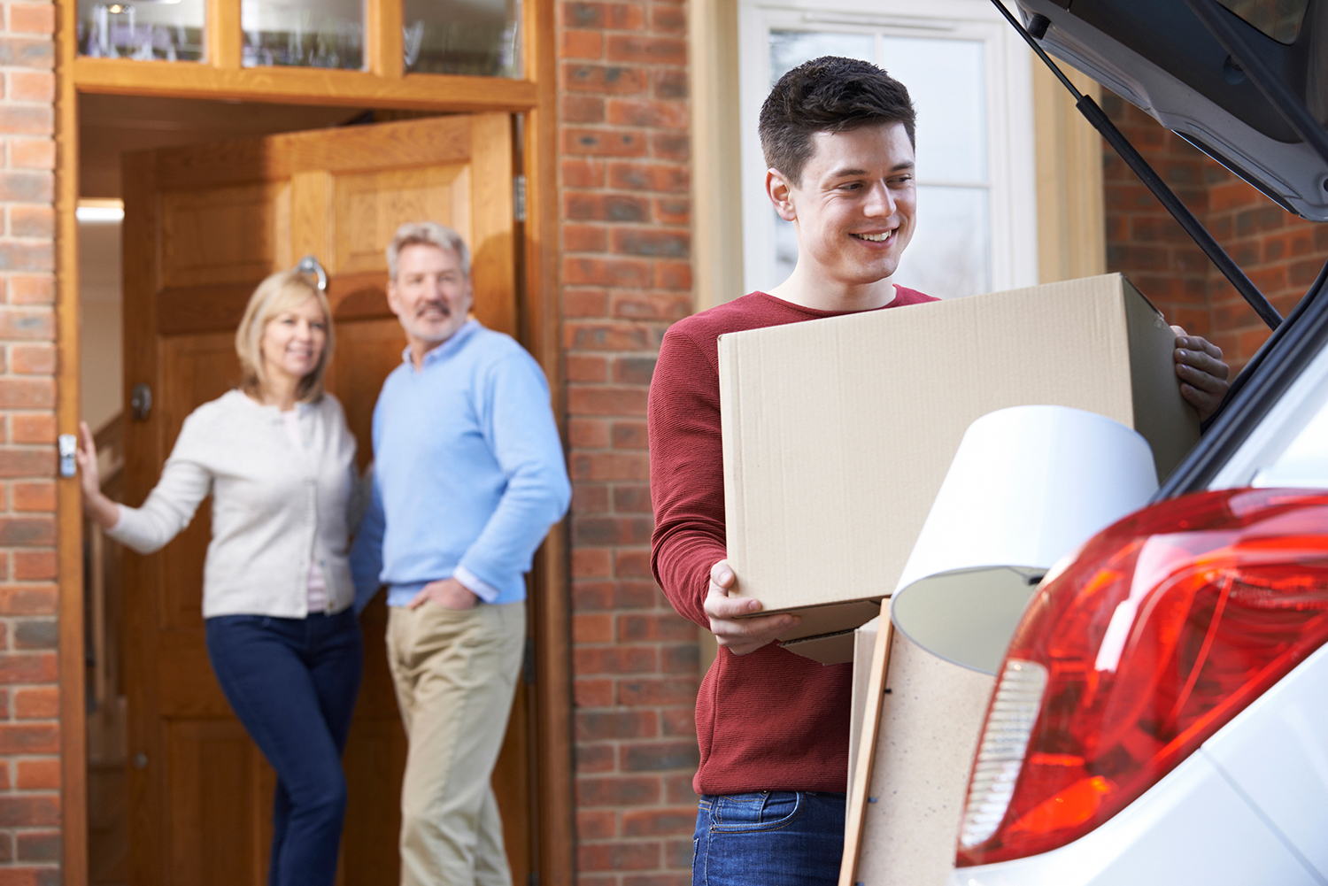 parents watching child loading car for college