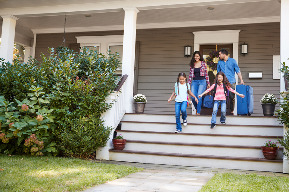family leaving front door of home to travel on vacation