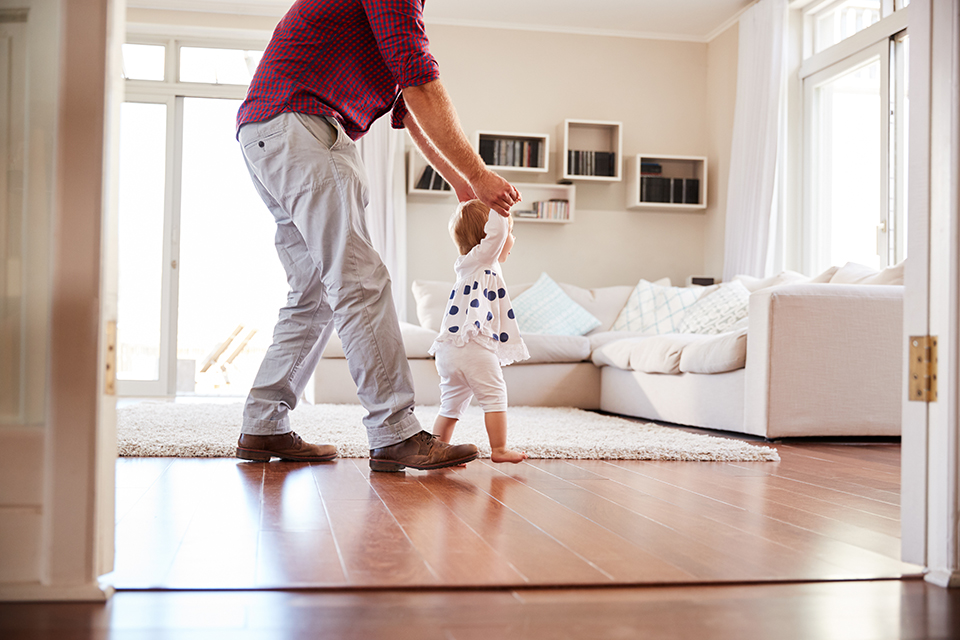father helping child walking across living room