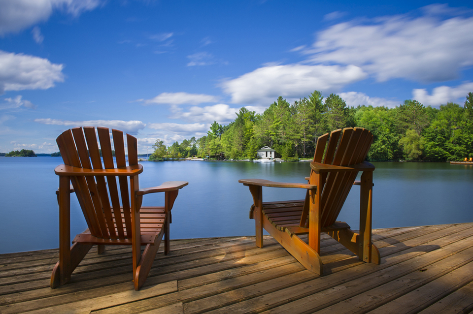 Two Muskoka chairs on a dock by the lake