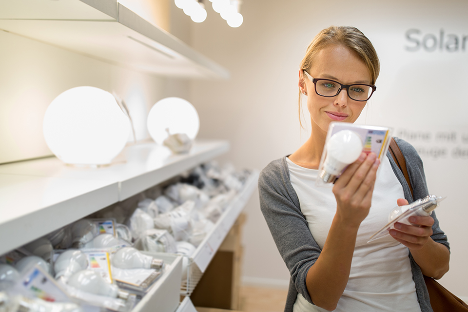 woman assessing her smart lighting options in store