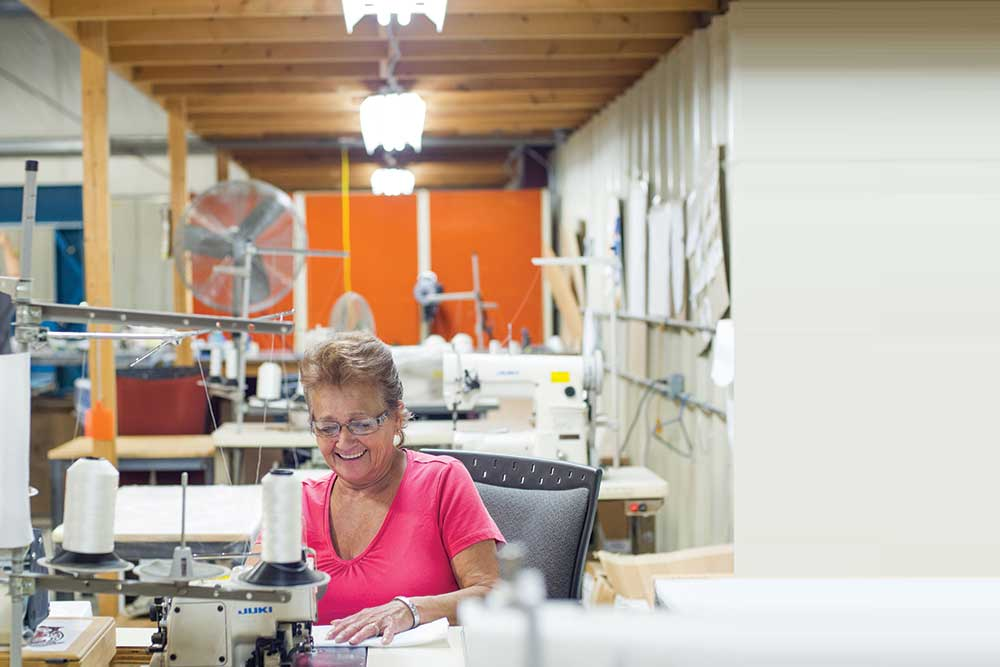 Seamstress sewing in a small and bright textile facility